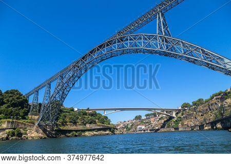Maria Pia Bridge over the Douro river, Porto, Portugal. View from the water. Wrought iron railway bridge. One of the most popular touristic destinations.