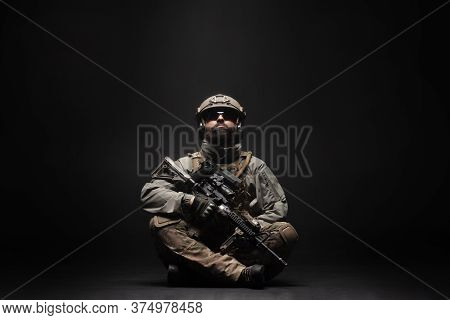 American Soldier In Military Equipment With A Rifle Sits On The Floor And Looks Up At The Copisse, T