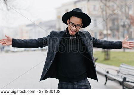 Lovable Young Man With Brown Skin Waving Hands On City Background. Outdoor Portrait Of Stylish Afric