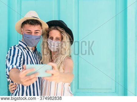 Young Couple Wearing Face Mask Taking Selfie With Mobile Smartphone On Vacation - People Having Fun