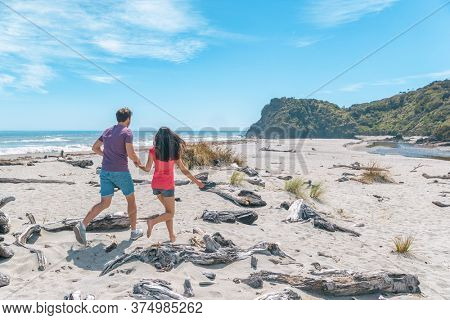 Couple walking on beach in New Zealand running having fun holding hands - young romantic couple in Ship Creek on West Coast of New Zealand. Tourist couple sightseeing South Island of New Zealand.