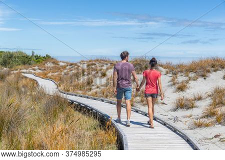 Couple walking on beach holding hands romantic in New Zealand - young people in Ship Creek on West Coast of New Zealand. Tourist couple sightseeing on South Island of New Zealand.
