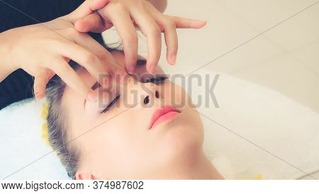 Relaxed Woman Lying On Spa Bed For Facial And Head Massage Spa Treatment By Massage Therapist In A L