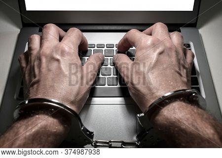 Hands in handcuffs typing on laptop keyboard concept for internet obsession or addiction