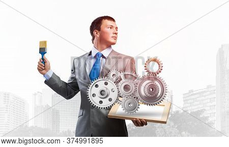 Creative Businessman Painter Holding Paint Brush And 3d Gears Mechanism. Portrait Of Young Man In Bu