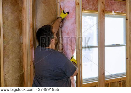 Construction Worker Thermally Insulating Insulation Layer Under House With Glass Wool