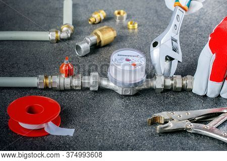 Plumber Fixing Water Meter With Adjustable Wrench.