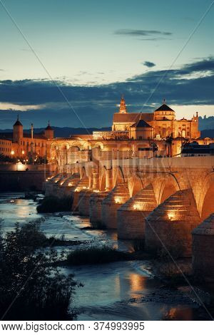 Mosque-Cathedral, ancient bridge and city skyline of Cordoba at night in Spain.