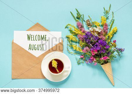 Welcome August Text On Paper Card In Craft Envelope, Cup Of Tea And Bouquet Field Flowers In Waffle