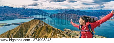 Hiker jumping of joy funny - panoramic banner of woman hiking in New Zealand laughing having fun, joyful and aspirational and carefree at Roys Peak, South Island, New Zealand.