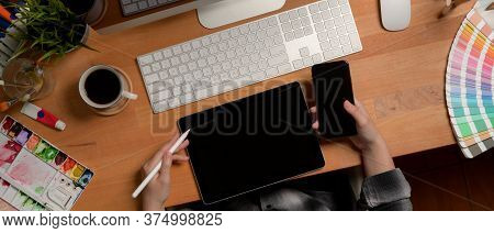 Female Designer Working With Digital Devices On Office Desk With Painting Tools And Supplies