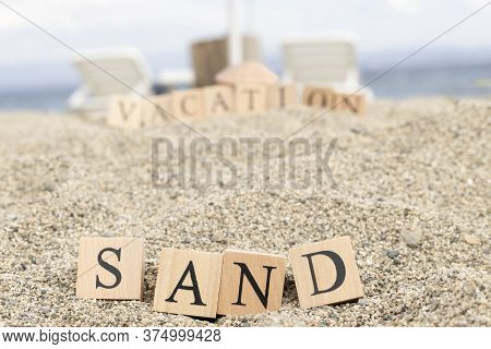 The Word Sand From Wooden Cubes. Close-up On The Beach Sand.