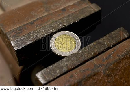 5 Zloty Coin In A Metal Vise. Concept Of Economic Problems. Selective Focus. Close Up