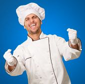 Portrait Of Male Chef Cheering On Blue Background poster