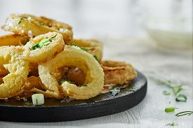 Onion Rings In Batter Sprinkled With Greens On A White Background In A Blur. Photo With Copy Space.