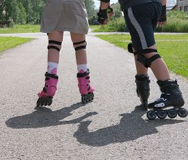 Brother And Sister Are Roller Skating Together. Family Support, Siblings Relationship Concept. Teena