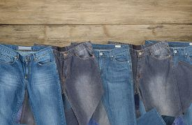 Jeans Folded On Brown Wooden Background, Top View With Copy Work Space.