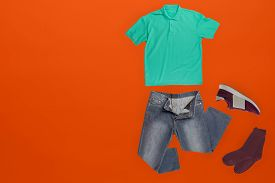 Flat Lay, Mens Fashion.grey Jeans , Red Sneakers, Gren T-shirt, Dark Red Socks On Ornge Background.