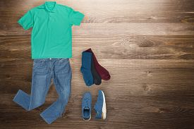 Flat Lay, Mens Fashion.blue Jeans , Blue Sneakers, Green T-shirt, Several Color Socks On A Wooden Ba