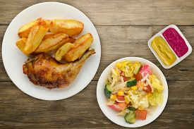 Chicken Thigh With French Fries On A Wooden Background. Chicken Thigh On A White Plate With Vegetabl
