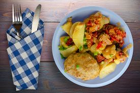 Cutlets With Potatoes And Stewed Tomatoes Top View. Cutlet On Light Blue Plate With Fork And Knife O