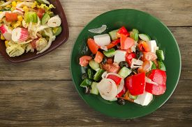 Greek Salad On Brown Wooden Background . Greek Salad On Green Plate With Vegetarian Salad Top View .
