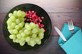 Grapes, Pomegranate On A Purple Wooden Background. Grapes, Pomegranate On A Black Plate With Fork An