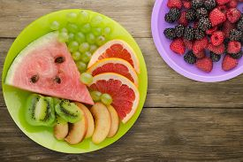 Sliced Fruit On A Borwn Wooden Background. Sliced Fruit On A Light Green Plate Wit Fruits On A Purpl