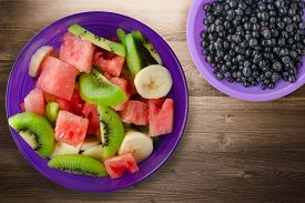 Purple Plate Of Healthy Fresh Fruit Salad On Brown Wooden Background .fruits Top View.vegetarian Foo
