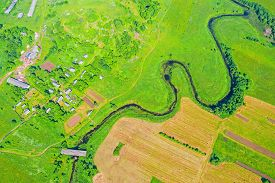 Top Aerial View Of The Natural Rural Landscape Valley Of A Meandering River Among Green Fields And F