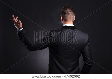 back view of an elegant young fashion man in tuxedo holding a cigar in his raised hand .on black background