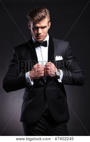elegant young fashion man in tuxedo holding both his hands on his collar while looking at the camera.on black background