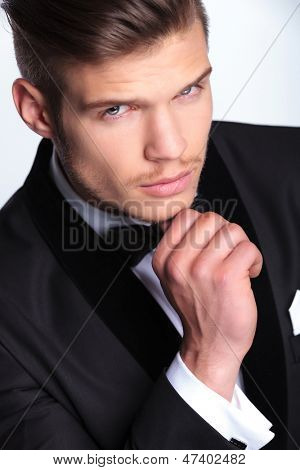 closeup picture of an elegant young fashion man in tuxedo looking pensively at the camera with his hand at his chin. on gray background
