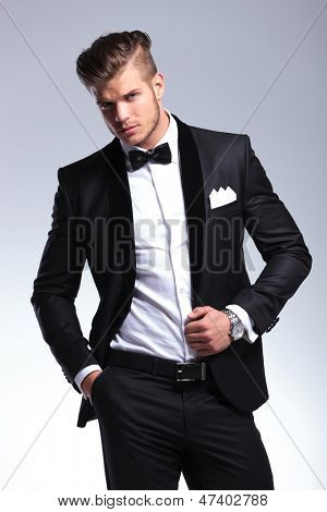 elegant young fashion man in an unbuttoned tuxedo looking at the camera. on gray background