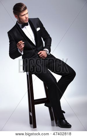 elegant young fashion man in tuxedo sitting on a chair and smoking while looking away from the camera. on gray background