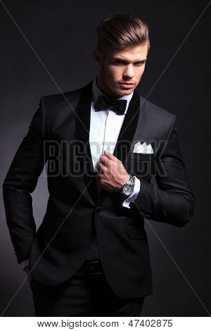 elegant young fashion man in tuxedo with a hand on his collar and the other in his pocket while looking at the camera.on black background