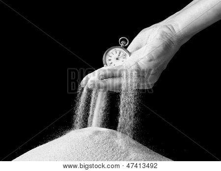 Female hand holding an antique pocket watch and sand flowing away