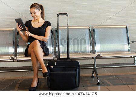 schöne junge Frau, die mit Tablet PC am Flughafen