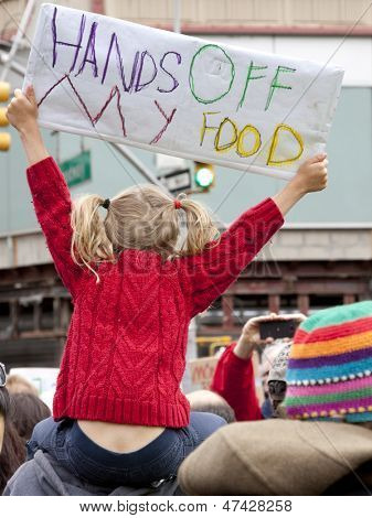 A young girl holds a sign that reads Hands Off My Food above the crowd during a march against genetically modified organisms, also known as GMO's.