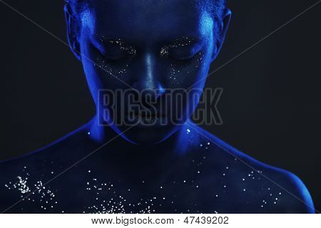 The beautiful young woman with a red mysterious mask over red background