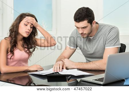 man upset after looking at card statement.