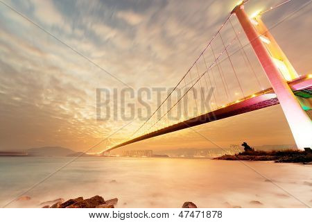Sunset cityscape with famous Tsing Ma bridge over water in Hong Kong, Asia.