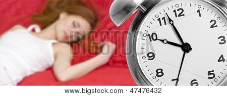 Alarm clock and sleeping young woman on background
