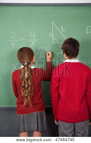 Rear view of teenage students solving mathematics on board in classroom