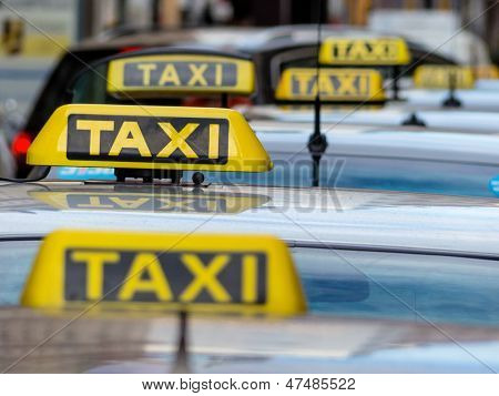 taxis wait at a taxi rank, symbol photo for passenger transport and services
