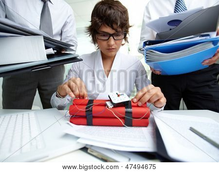 Serious secretary with dynamite being surrounded by big heaps of papers held by men