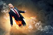 Image of young businessman in anger burning in fire poster