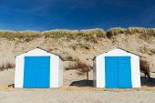 Row blue and white beach cabins for vacation surpose poster