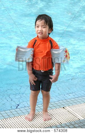Little Boy With Arm Floats & Swimming Costume By The Pool