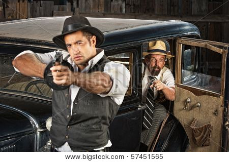 Tough 1920s vintage gangsters outside aiming guns from car poster